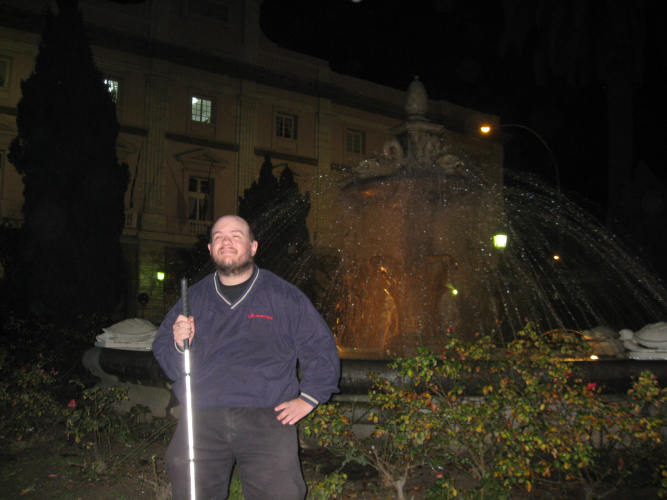 Tony standing in front of a fountain in the centre of Cadiz